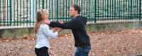 Man grabbing throat of woman walking on street